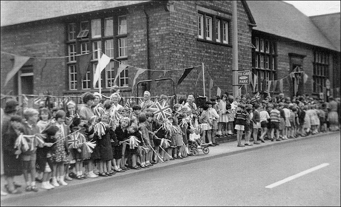 Children of Burton Latimer Council Schools await the drive-past of the Queen in July 1965