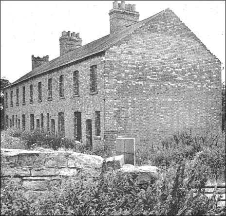 Photograph showing the row of derelict houses before getting a new lease of life