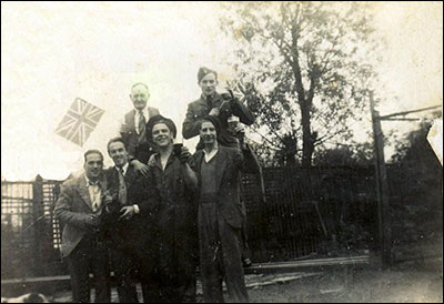 Photograph showing group with landlord apparently celebrating some World War 2 event.