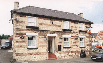 Recent photograph of The Waggon & Horses with car sales lot to the right.