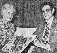 Mrs. Alice Dacre receiving a bouquet of flowers from Council Chairman  Nicholas Loake.